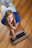 Muchacha en un suelo de madera que se relaja con una computadora portátil Imagen de archivo libre de regalías