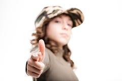 Muchacha en un tiroteo de color caqui del casquillo con sus fingeres Imágenes de archivo libres de regalías