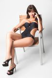 Muchacha en un traje de baño. el sentarse en una silla. Imágenes de archivo libres de regalías