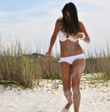 Muchacha en un traje de baño que recorre en la playa Foto de archivo