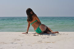 Muchacha en un traje de baño que se sienta en la playa fotografía de archivo