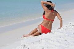 Muchacha en un traje de baño que se sienta en la playa Fotografía de archivo libre de regalías