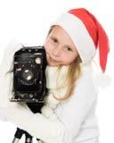 Muchacha en un traje de la Navidad con la cámara vieja Fotografía de archivo libre de regalías
