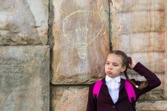 Muchacha en un uniforme escolar que piensa, una bombilla pintada en la pared Foto de archivo