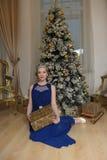 Muchacha en un vestido azul en el árbol de navidad con un regalo a disposición y una corona Fotos de archivo