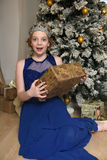 Muchacha en un vestido azul en el árbol de navidad con un regalo a disposición y una corona Foto de archivo