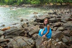 Muchacha en un vestido azul en las rocas de la costa de mar Fotografía de archivo libre de regalías