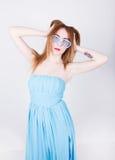 Muchacha en un vestido azul y gafas de sol en el estilo del disco, aumentado sus manos al top y tocado su pelo Fotos de archivo