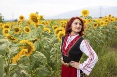 Muchacha en un vestido búlgaro tradicional en un campo de girasoles foto de archivo