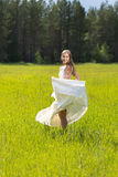 Muchacha en un vestido blanco en un campo Foto de archivo libre de regalías
