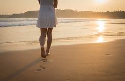 Muchacha en un vestido blanco que camina a lo largo de la playa del océano Vista de la pierna fotografía de archivo libre de regalías