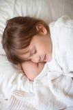 Muchacha en un vestido brillante que duerme en la cama Fotografía de archivo libre de regalías