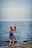 Muchacha en un vestido colorido en el embarcadero imagenes de archivo