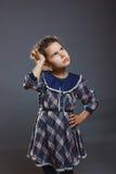 Muchacha en un vestido colorido que mira para arriba y que se pregunta Imagen de archivo libre de regalías