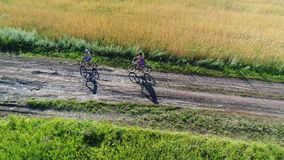 Muchacha en un vestido con un niño que monta una bicicleta a lo largo de campos del trigo Tiroteo con el abejón Paisaje hermoso d metrajes