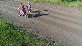 Muchacha en un vestido con un niño que monta una bicicleta a lo largo de campos del trigo Tiroteo con el abejón Paisaje hermoso d almacen de video