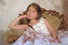 Muchacha en un vestido de bola elegante que se sienta en una butaca grande Fotografía de archivo libre de regalías
