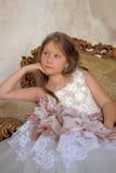 Muchacha en un vestido de bola elegante que se sienta en una butaca grande Foto de archivo