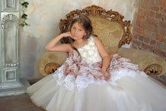 Muchacha en un vestido de bola elegante que se sienta en una butaca grande Fotos de archivo