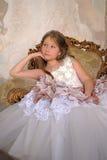 Muchacha en un vestido de bola elegante que se sienta en una butaca grande Foto de archivo libre de regalías