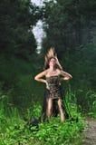 Muchacha en un vestido de noche negro en la madera Imagen de archivo libre de regalías