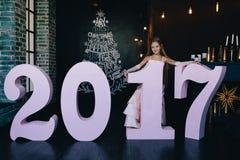 Muchacha en un vestido festivo que se coloca con los números grandes 2017 Concepto 2017 de la Feliz Año Nuevo Fotos de archivo libres de regalías