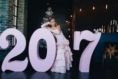 Muchacha en un vestido festivo que se coloca con los números grandes 2017 Concepto 2017 de la Feliz Año Nuevo Foto de archivo