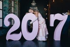 Muchacha en un vestido festivo que se coloca con los números grandes 2017 Concepto 2017 de la Feliz Año Nuevo Fotografía de archivo