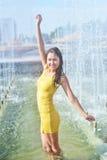 Muchacha en un vestido furtivo corto con el pelo y las piernas mojados largos en gotitas de agua en la fuente de la ciudad Imagen de archivo