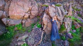 Muchacha en un vestido largo contra la perspectiva de una roca Imágenes de archivo libres de regalías