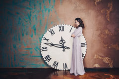 Muchacha en un vestido largo sobre el reloj grande Imagen de archivo libre de regalías