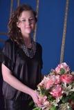 Muchacha en un vestido negro al lado de un florero con las flores Foto de archivo