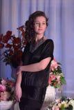 Muchacha en un vestido negro al lado de un florero con las flores Imagen de archivo libre de regalías