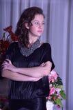Muchacha en un vestido negro al lado de un florero con las flores Fotos de archivo