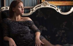Muchacha en un vestido negro en sitio de lujo Fotos de archivo
