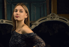 Muchacha en un vestido negro en sitio de lujo Imagen de archivo libre de regalías