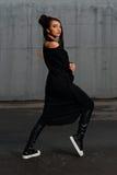 Muchacha en un vestido negro que presenta en el estacionamiento Fotos de archivo libres de regalías