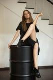 Muchacha en un vestido negro que se sienta en un barril-rollo negro debajo de las escaleras Imagen de archivo libre de regalías