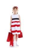 Muchacha en un vestido rayado que sostiene los paquetes rojos Fotografía de archivo