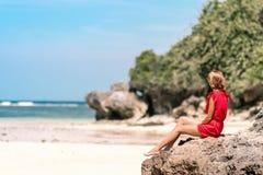 Muchacha en un vestido rojo que se sienta descalzo en la piedra cerca de la orilla de mar Playa tropical, isla de Bali Día asolea fotos de archivo libres de regalías