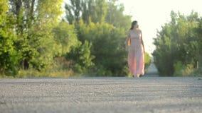 Muchacha en un vestido rosado que camina en el camino almacen de metraje de vídeo