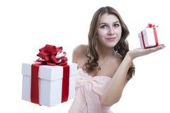 Muchacha en un vestido rosado que sostiene una caja de regalo Imagen de archivo