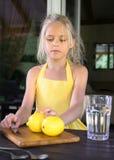 Muchacha en un vestido, un limón y una limonada amarillos Foto de archivo