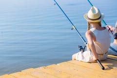 Muchacha en un vestido y un sombrero con una caña de pescar Imagenes de archivo