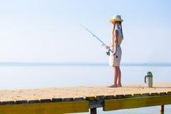Muchacha en un vestido y un sombrero con una caña de pescar Imagen de archivo libre de regalías