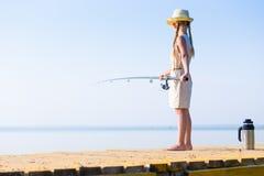 Muchacha en un vestido y un sombrero con una caña de pescar Fotografía de archivo
