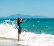 Muchacha en un wetsuit en la playa Imagen de archivo