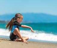 Muchacha en un wetsuit en la playa Fotografía de archivo