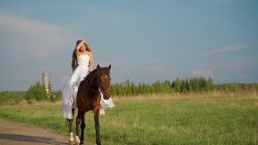 Muchacha en una alineada blanca en un caballo Novia que monta un caballo en el campo metrajes