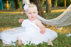 Muchacha en una alineada de boda blanca en la hierba Imagenes de archivo